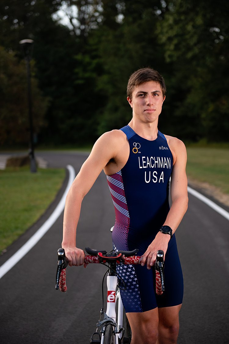 High school senior boy in USA bike suit standing beside bike on curved paved road at Hartwood Acres in Pittsburgh, PA