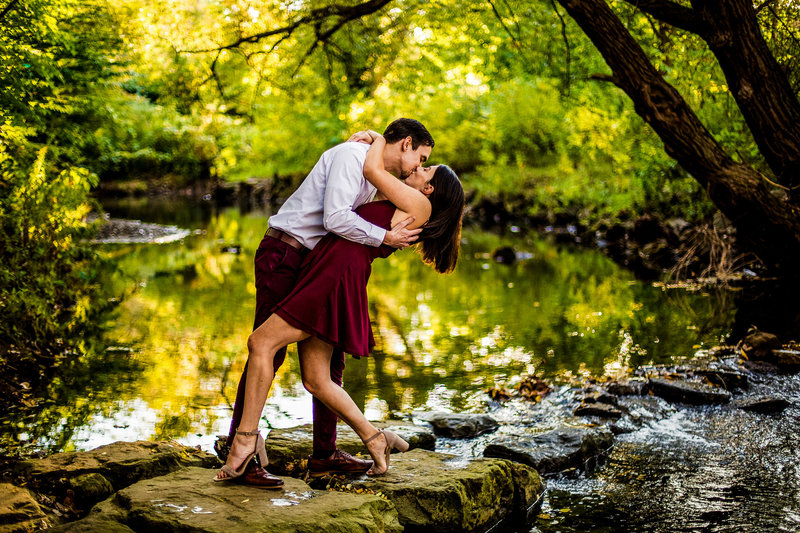 Man kisses and dips his fiancee next to Cascade Creek during engagement photo session at Frontier Park