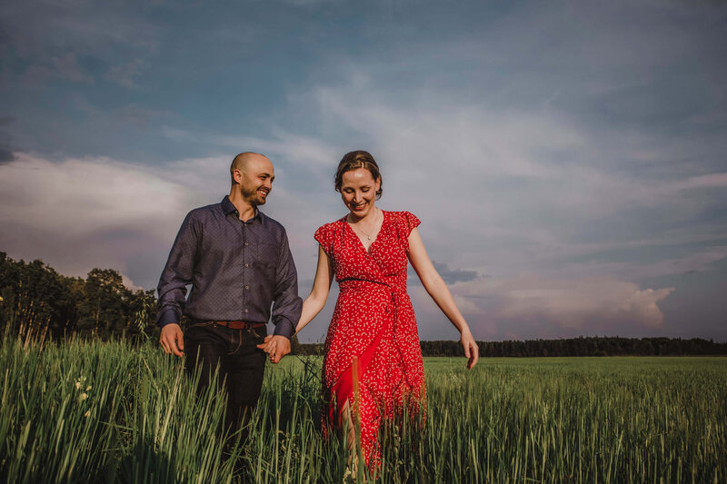 engaged couple walks hand in hand through wheat field