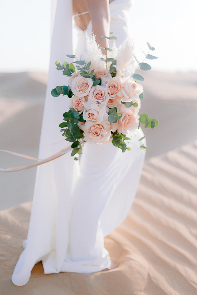 bride holding a bouquet of flower in the desert of budai during a photoshoot with wedding photographer gabriella vanstern