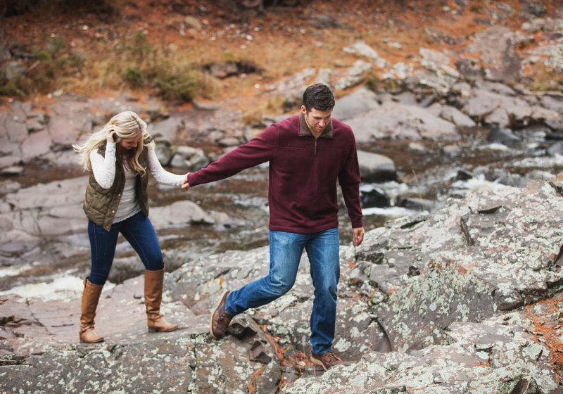 Engaged couple, holding hands, walking up rock shore of Lester River in Duluth Minnesota.