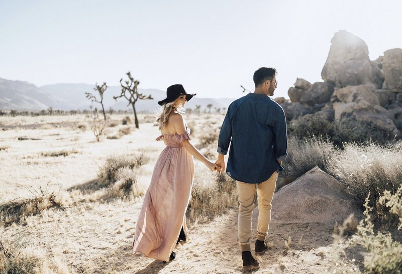 bree and stephen holding hands and walking in joshua tree national park while working an eleopement