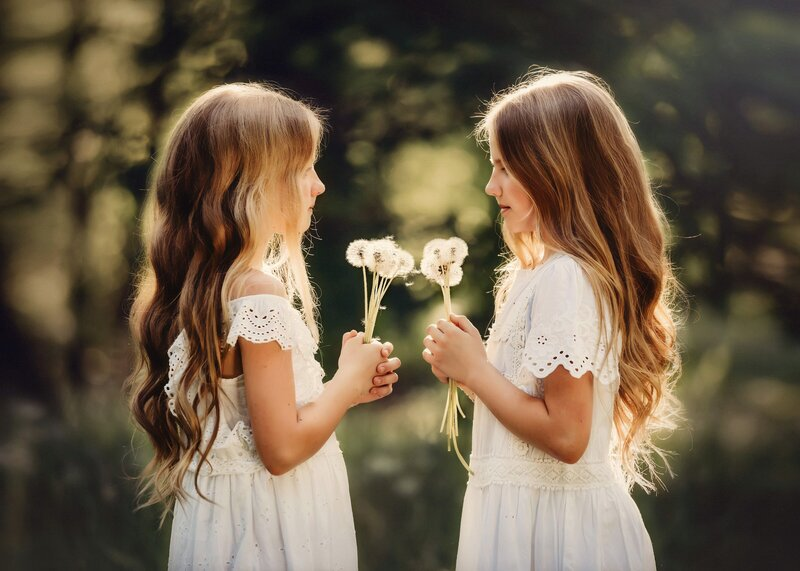 Sisters face each other in a field holding bouquets of dandelions