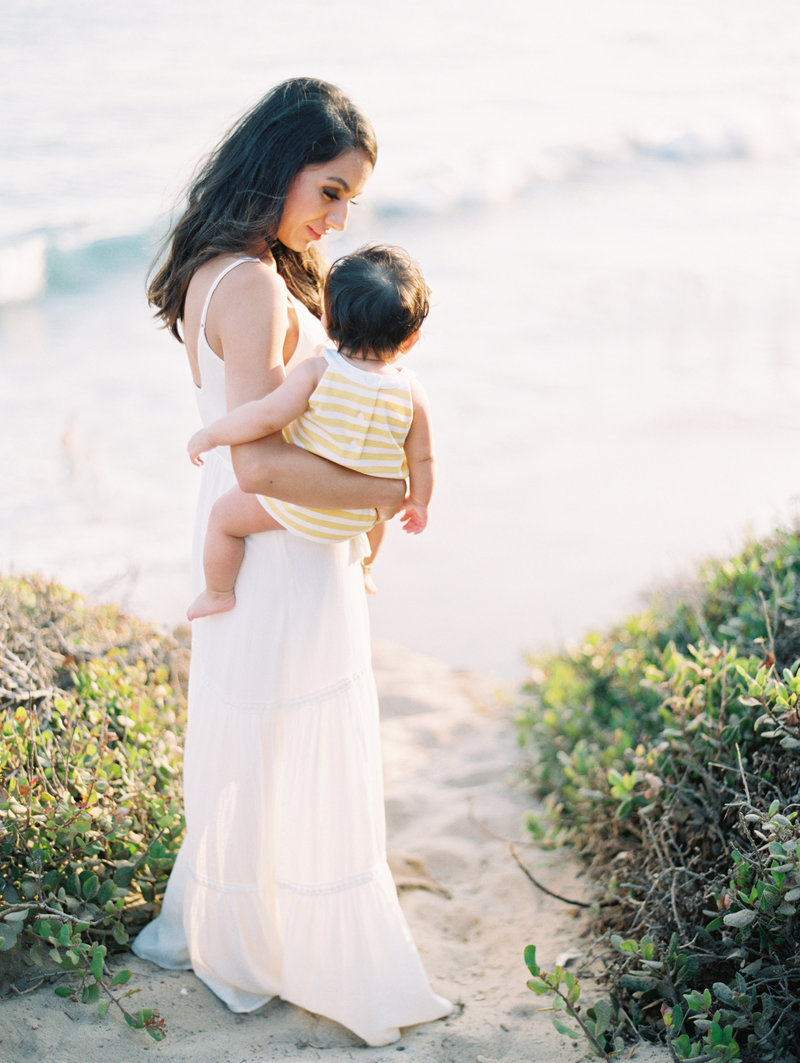 Mother holding baby on her hip during her family portrait session in Malibu at El Matador Beach