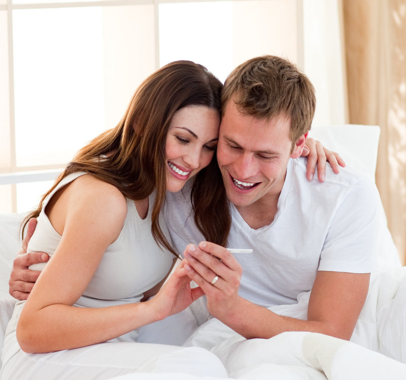 Couple smiling at pregnancy test