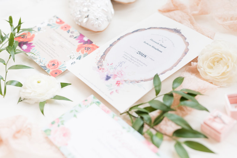 Watercolor invitation suite sits on board.