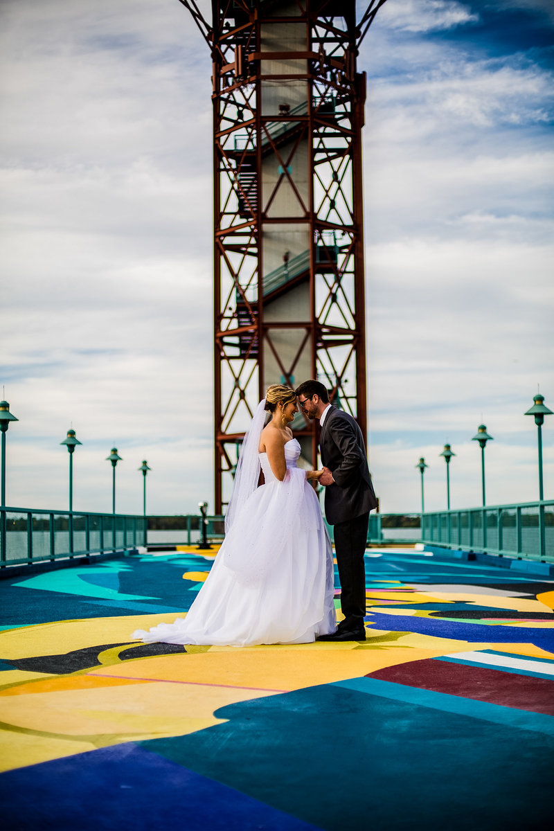 Bride and groom holding hands and touching foreheads in front of the Bicentennial Tower in Erie, PA