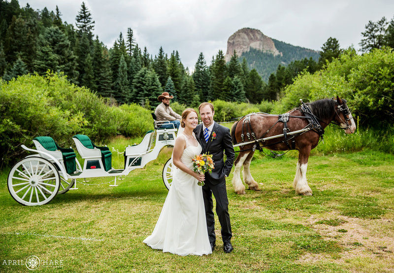 Couple pose with the horse drawn carriage at Mountain View Ranch in Colorado