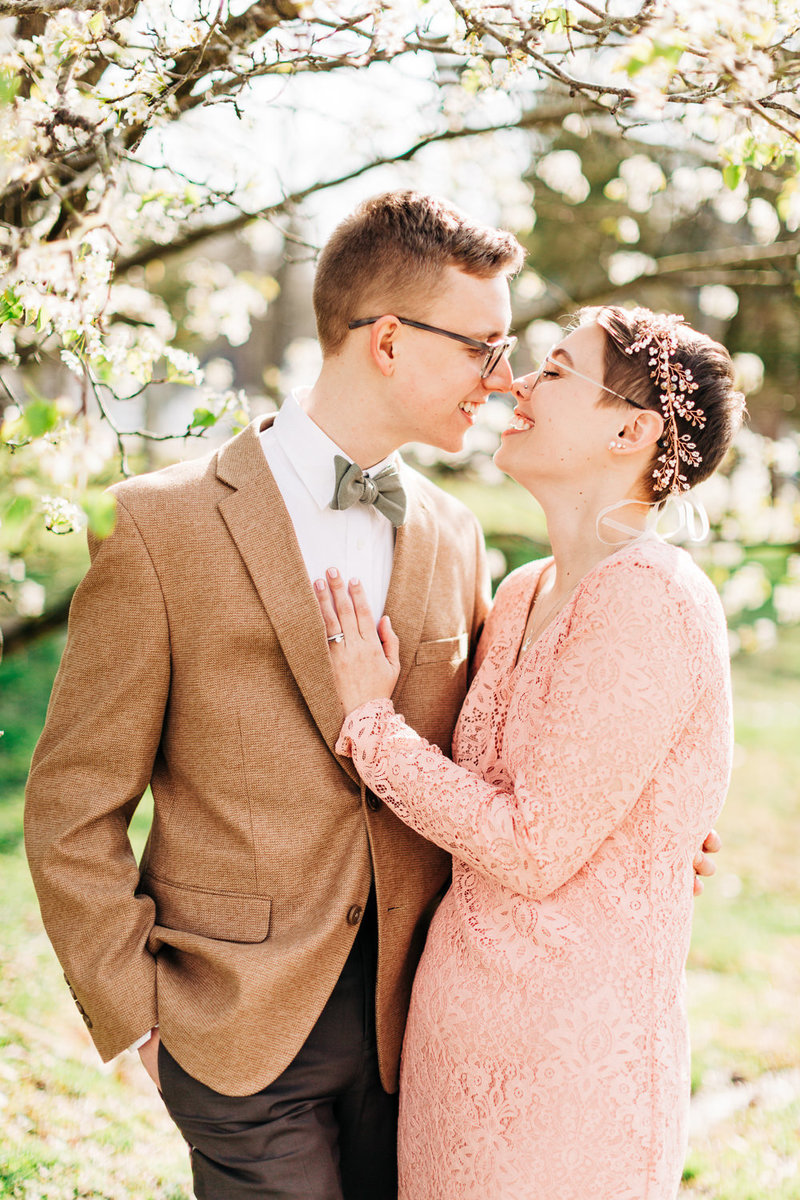 newly eloped couple smiles and bumps noses under a blooming tree
