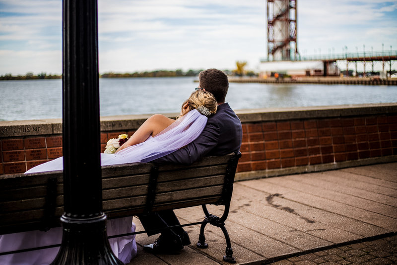Bride and groom sitting on a bench outside the Sheraton Erie Bayfront Hotel