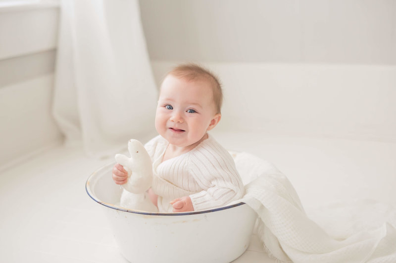 smiling baby sitting in a white bucket in houston photography studio