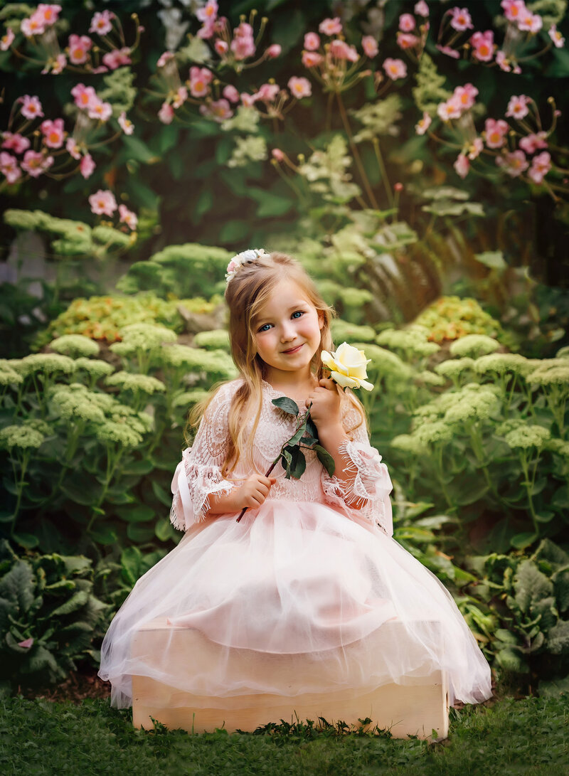Young girl in pink party dress smiles for photo holding a rose