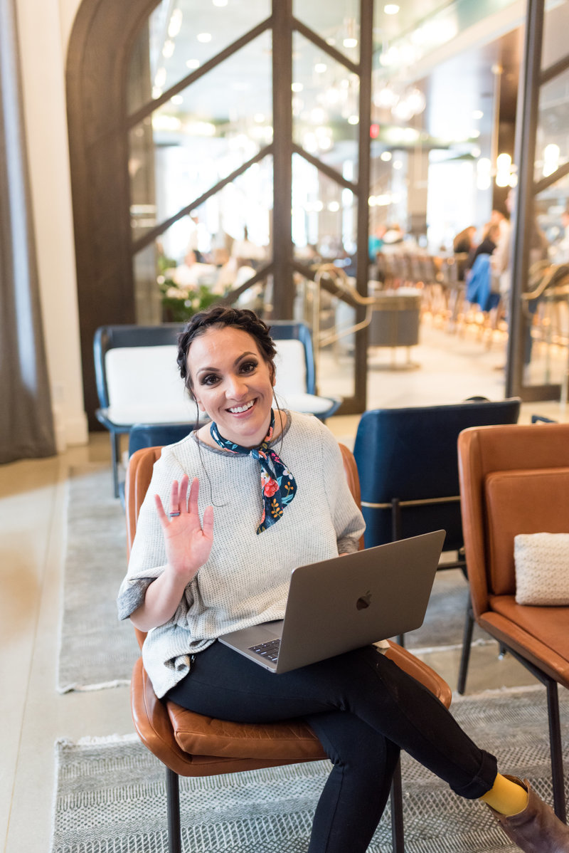 Friendly Woman Waving To the Camera as she looks up from her laptop  and workspace