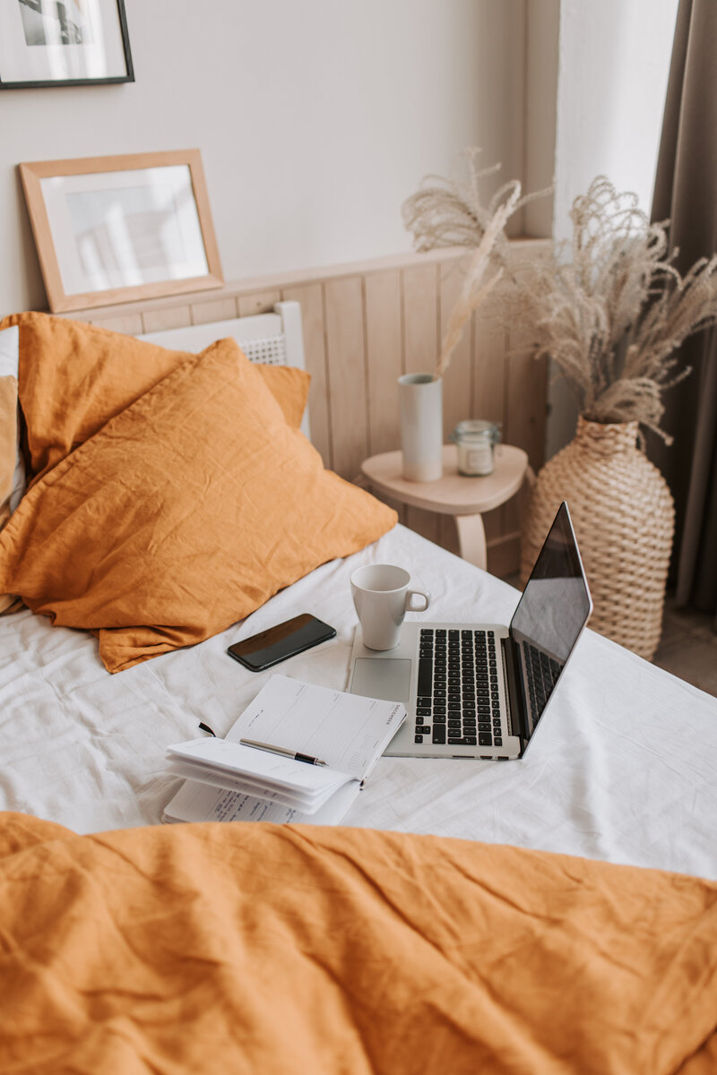 laptop-with-copybook-and-cup-of-coffee-on-bed-sheet-4050430