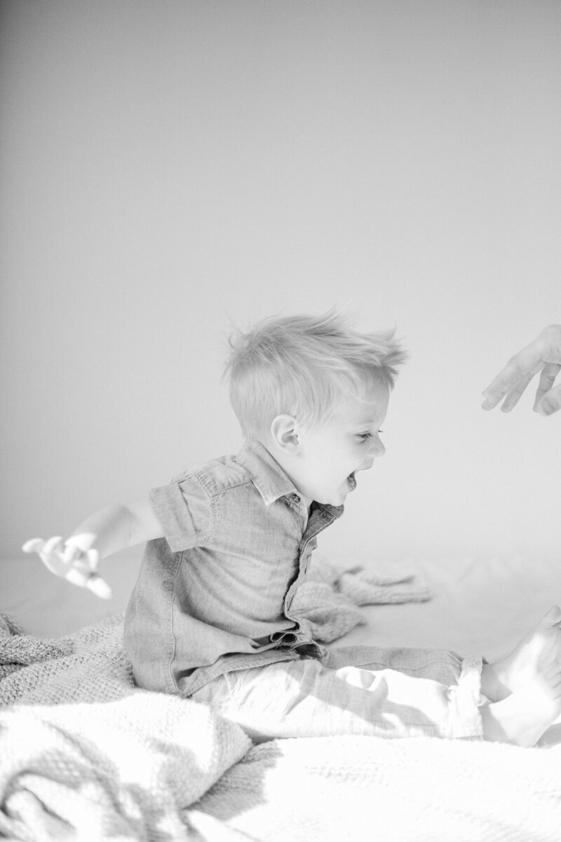 Black and white family portrait of a toddler playing during an in-home Rochester family photography session.