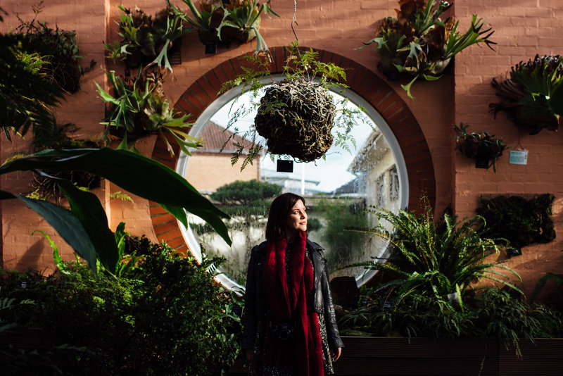 photo of charlie standing in front of large circular window surrounded by greenery in Birmingham botanical gardens