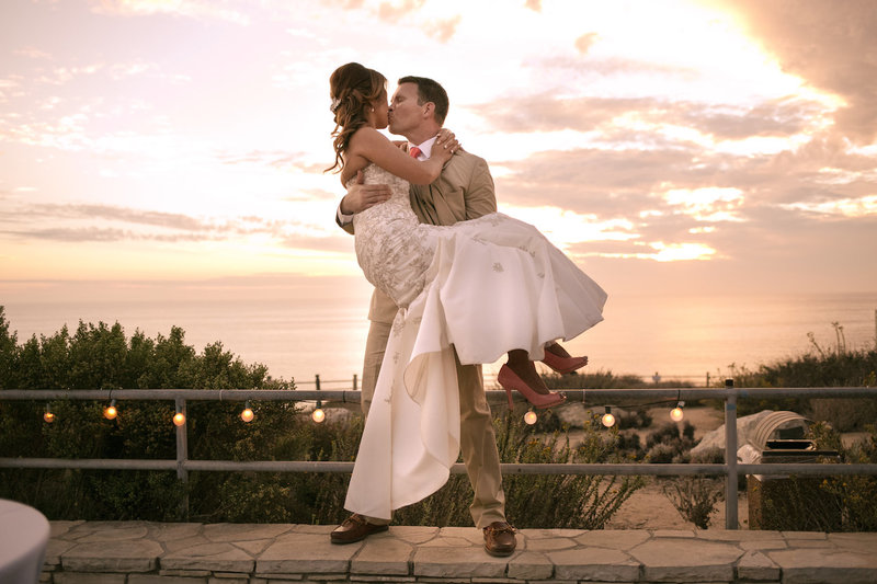 Newly married bride and groom, outside at Point Vicente, embracing during sunset