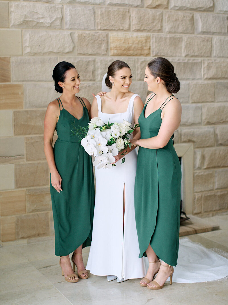 Bride and bridesmaids smiling at each other in front of a sandstone wall