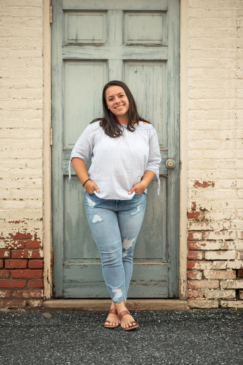 Senior girl in jeans in front of distressed door and brick wall