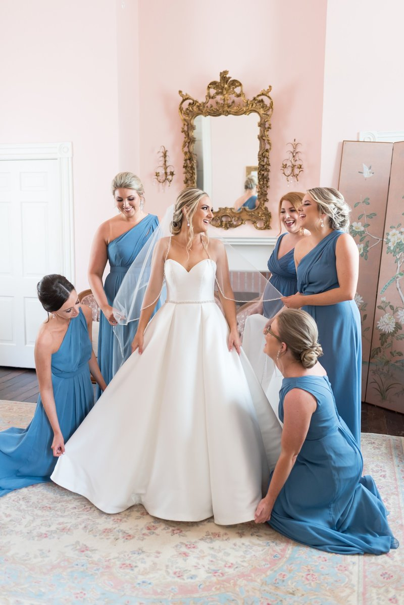 Bride in wedding gown with bridesmaids in blue dresses surrounding her at Ravenswood Mansion