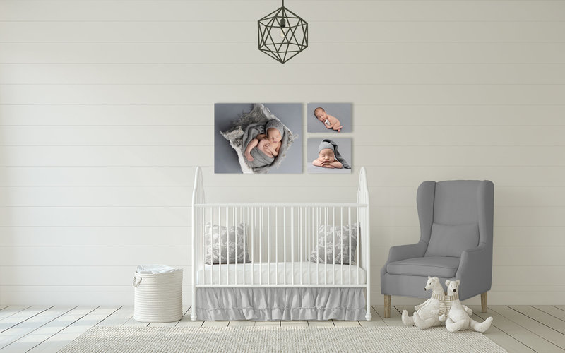 Canvas wall gallery of newborn images behind crib in nursery