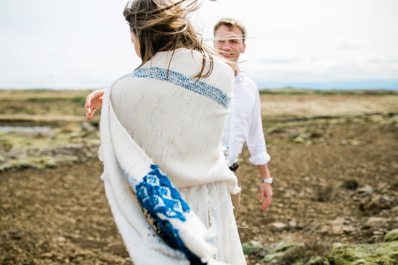 the bride wraps herself in a shawl during her iceland elopement