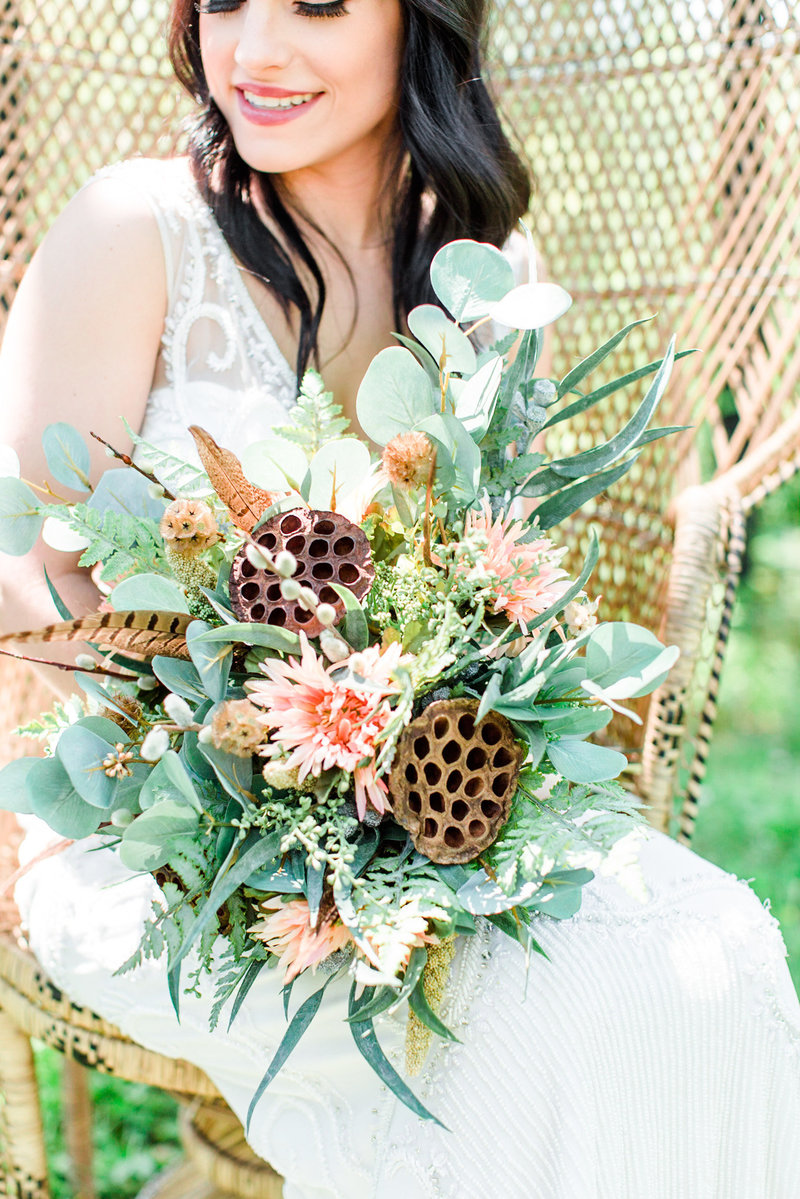 bride detail shot with bride holding a honeycomb bouquet in a wicker chair