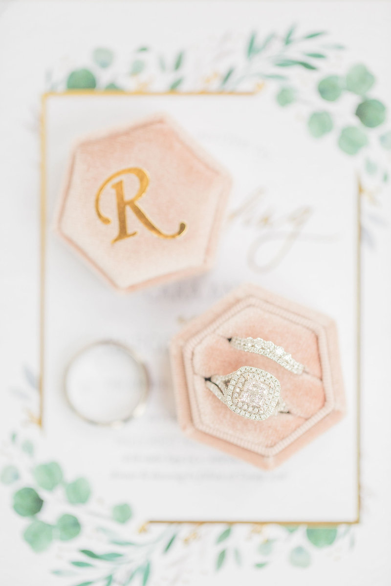 wedding day details shots, rings in box on invitation