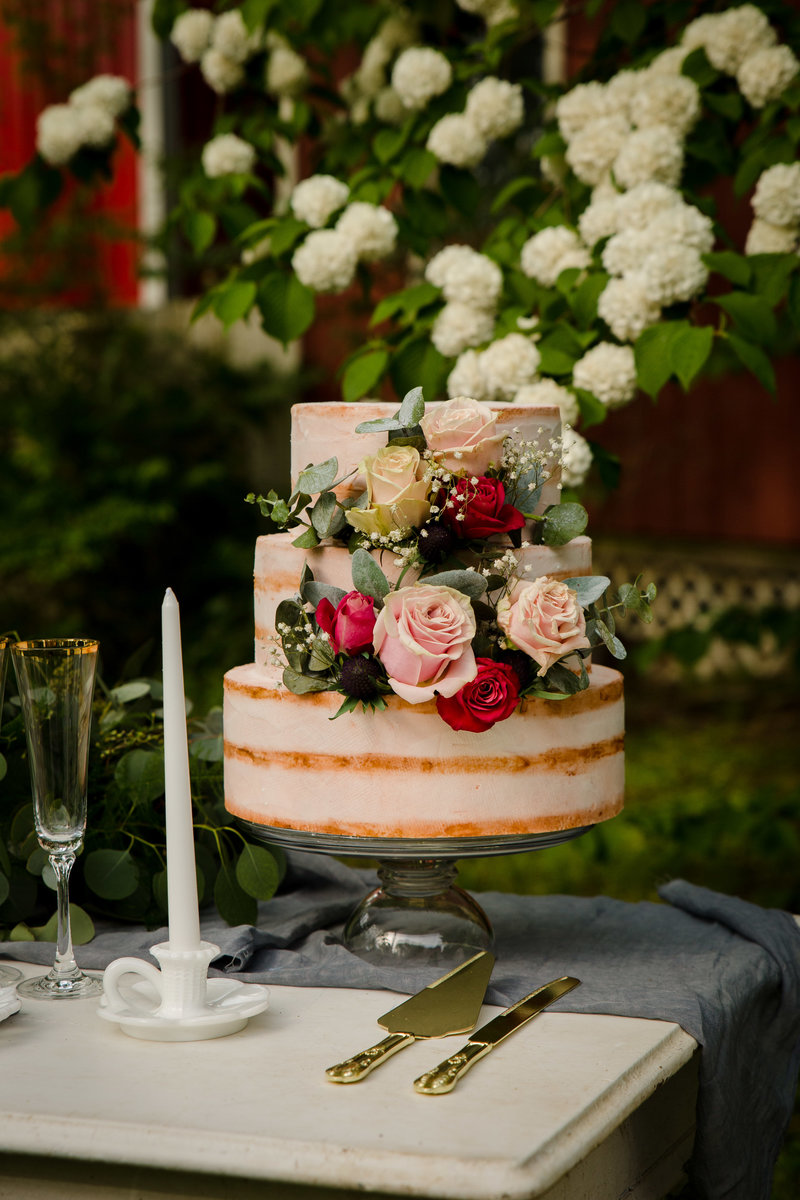 beautiful naked wedding cake with cascading flowers