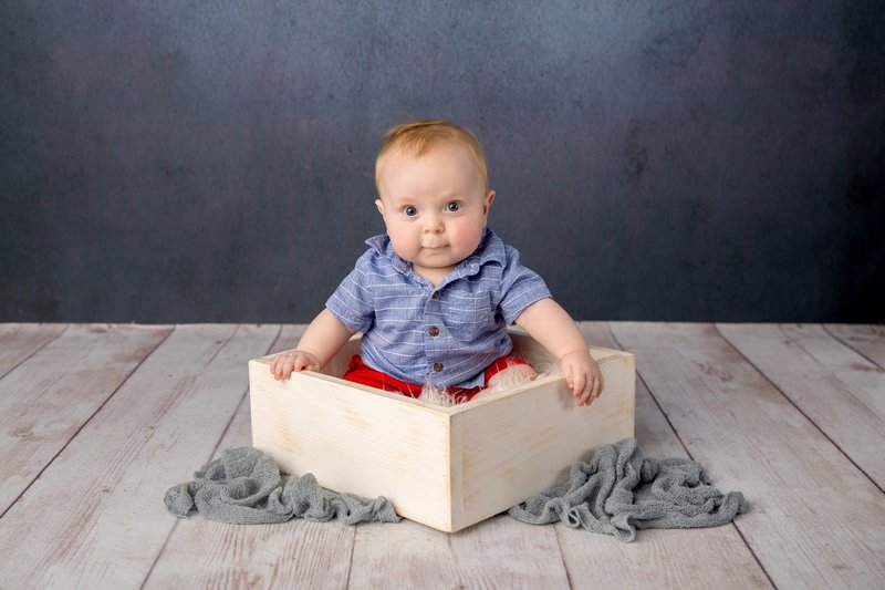 baby boy sits in a white box against a blue background