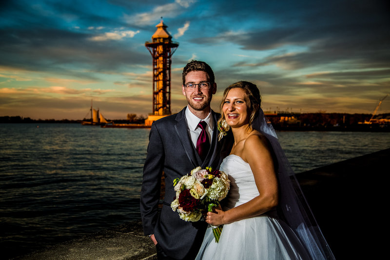 Bride and groom outside the Sheraton Erie Bayfront Hotel at sunset with Bicentennial Tower in background