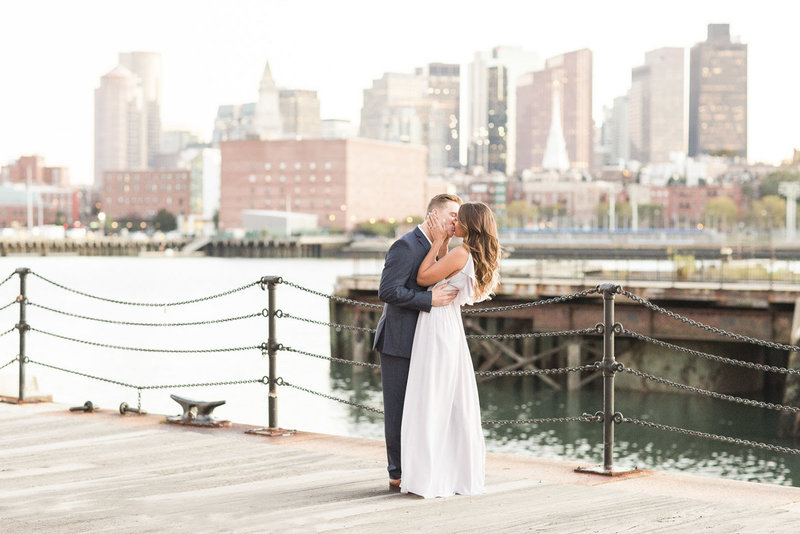 Couple kissing in front of Boston skyline