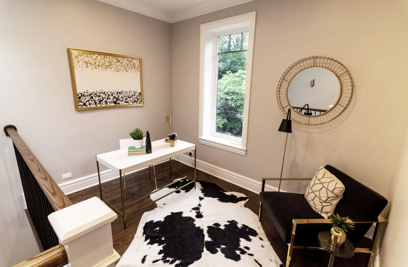 Magnolia office area above stairs with a white desk and desk chair and a black suede arm chair accented with brass accessories and art