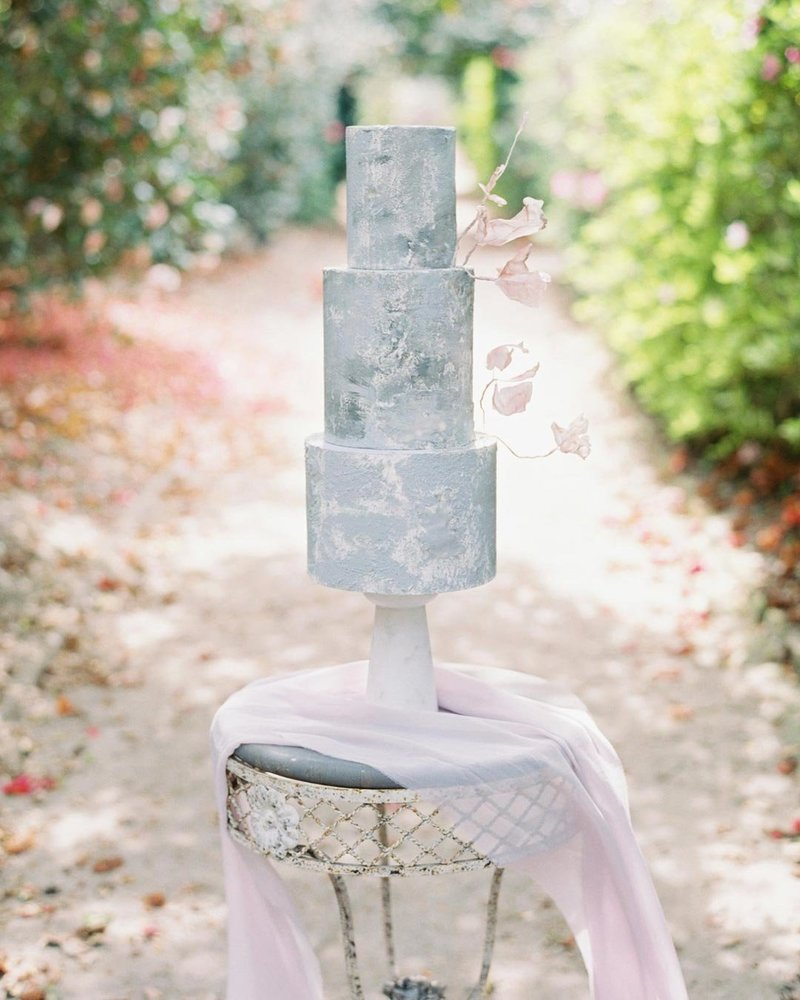 Concrete textured wedding cake with rice paper flowers and a silk lilac runner