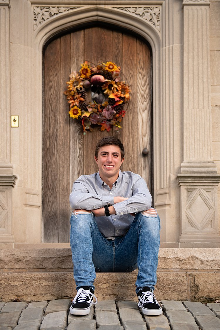High school senior boy seated in front of brown wooden door with fall wreath at Hartwood Acres in Pittsburgh, PA