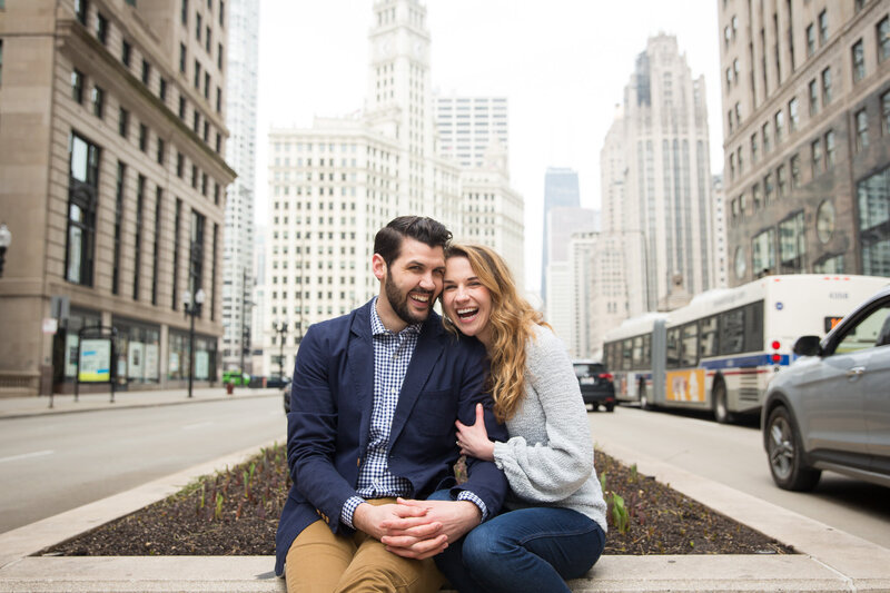 couple on michigan avenue laughing after surprise proposal in downtown chicago
