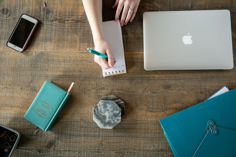 Desk overlay with a Mac laptop, notepad, coasters, cell phone, teal notebook, and antique wooden desk
