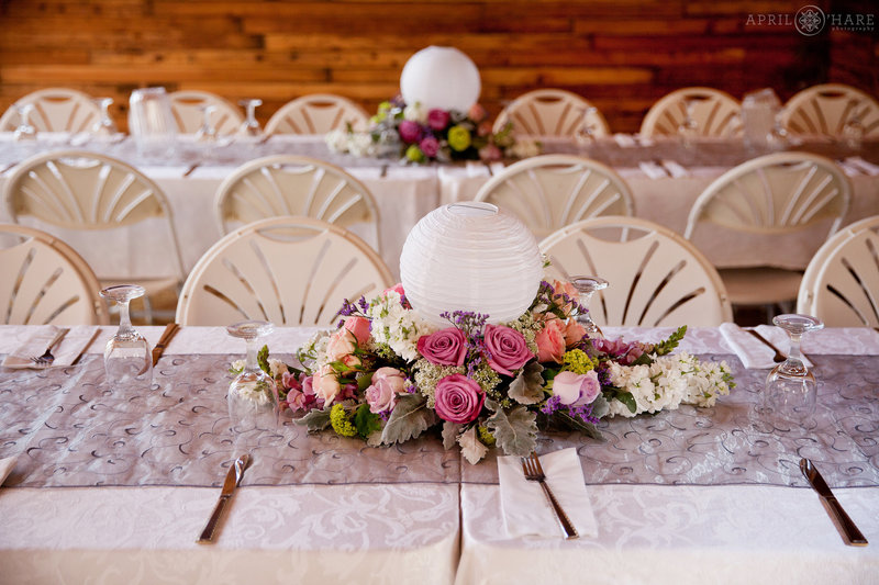 Pretty Long White Tables with purple and pink florals at Mountain View Ranch Barn Reception