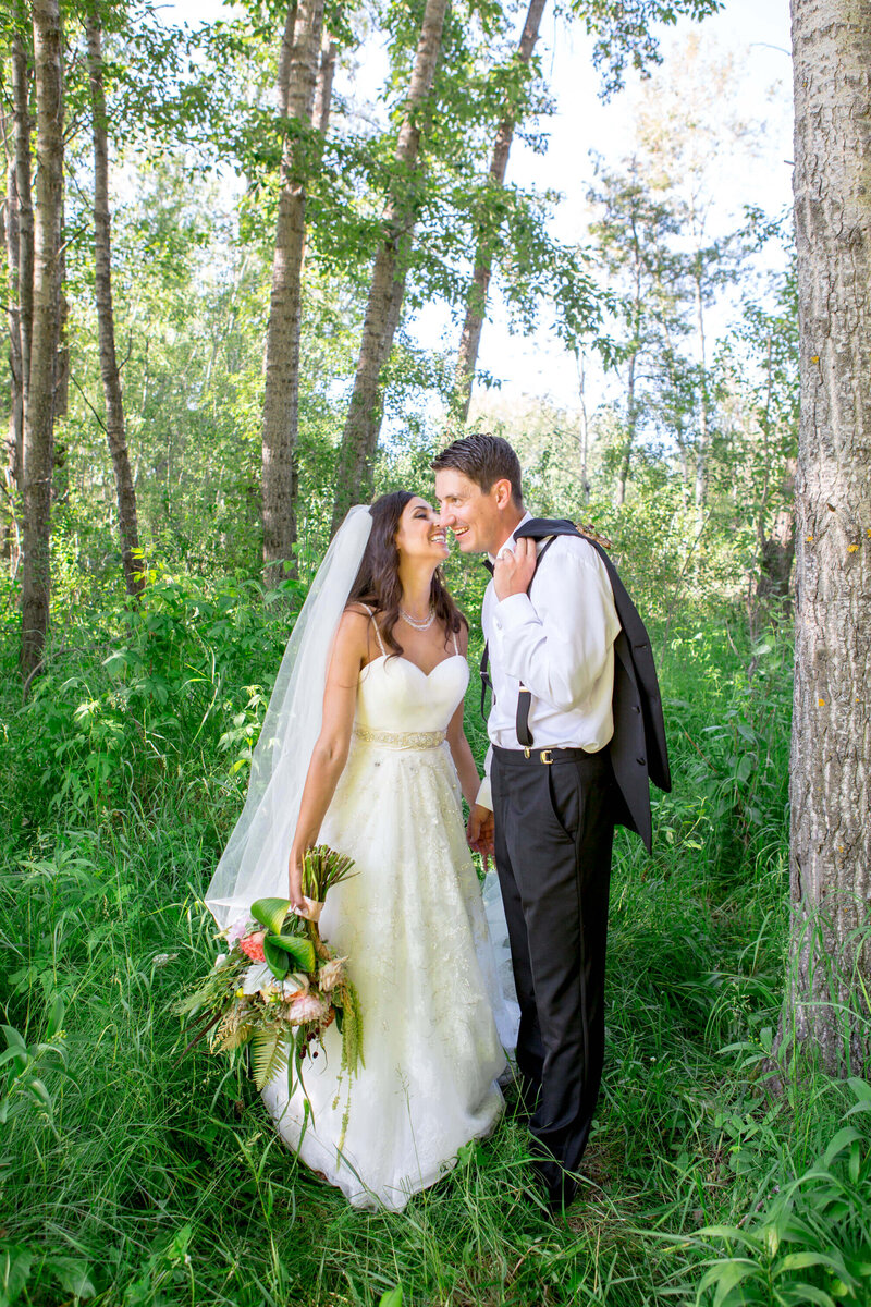bride kisses groom on cheek in the forest