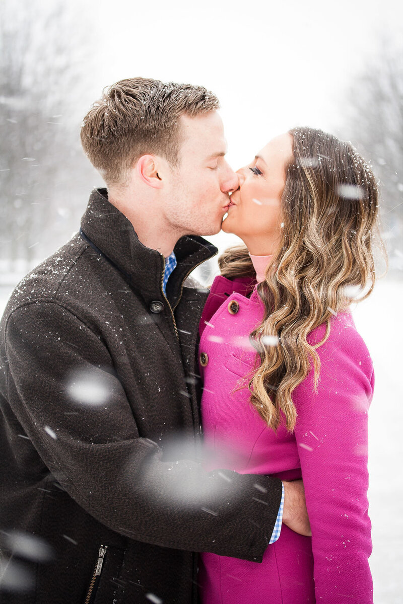 kissing during snowy winter engagement session in Millennium Park Chicago