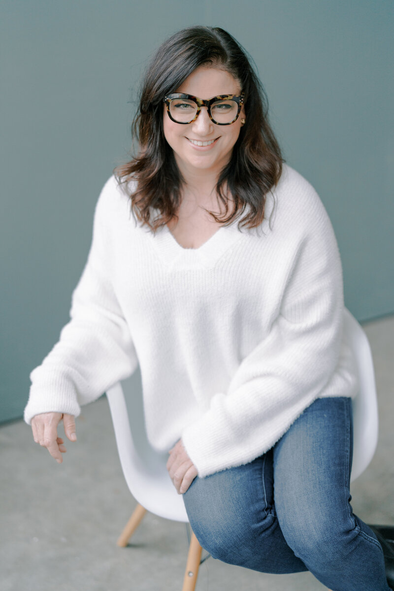 woman in a white fuzzy sweater sitting in a white chair with dark rimmed glasses on smiling at the camera
