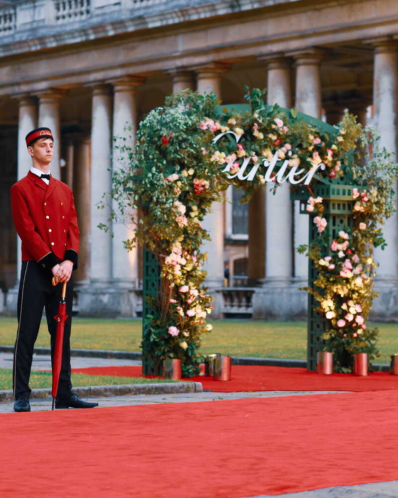 A red carpet with a floral arch at the Old Royal Naval College in London for an event for Cartier.