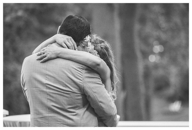 Candid black and white photo of a bride and groom hugging.