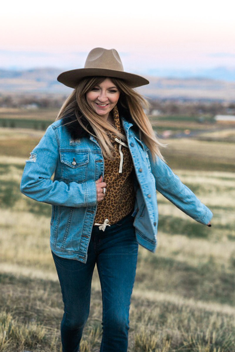 Stephanie with a jean jacket and hat on running through a field in Utah