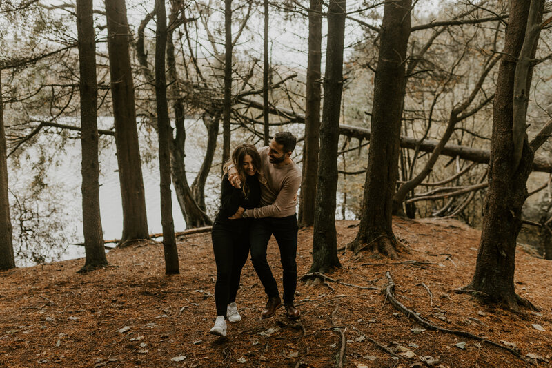 Couple in woods laughing and cuddling walking