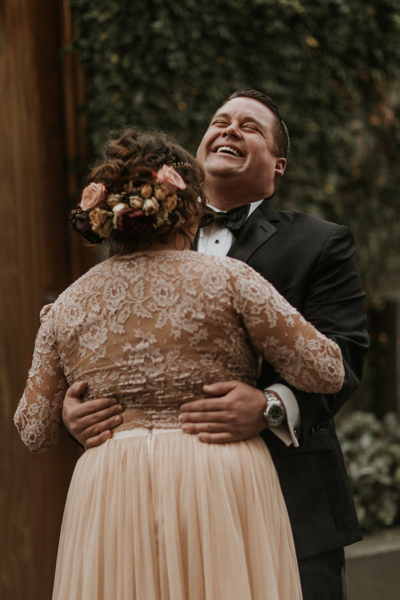 Bride in lace blush wedding dress and floral crown with groom in tuxedo at Natural History Museum wedding on New Years Eve
