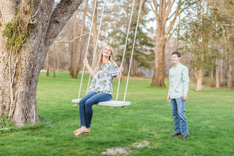 engaged couple laughing outside on swing