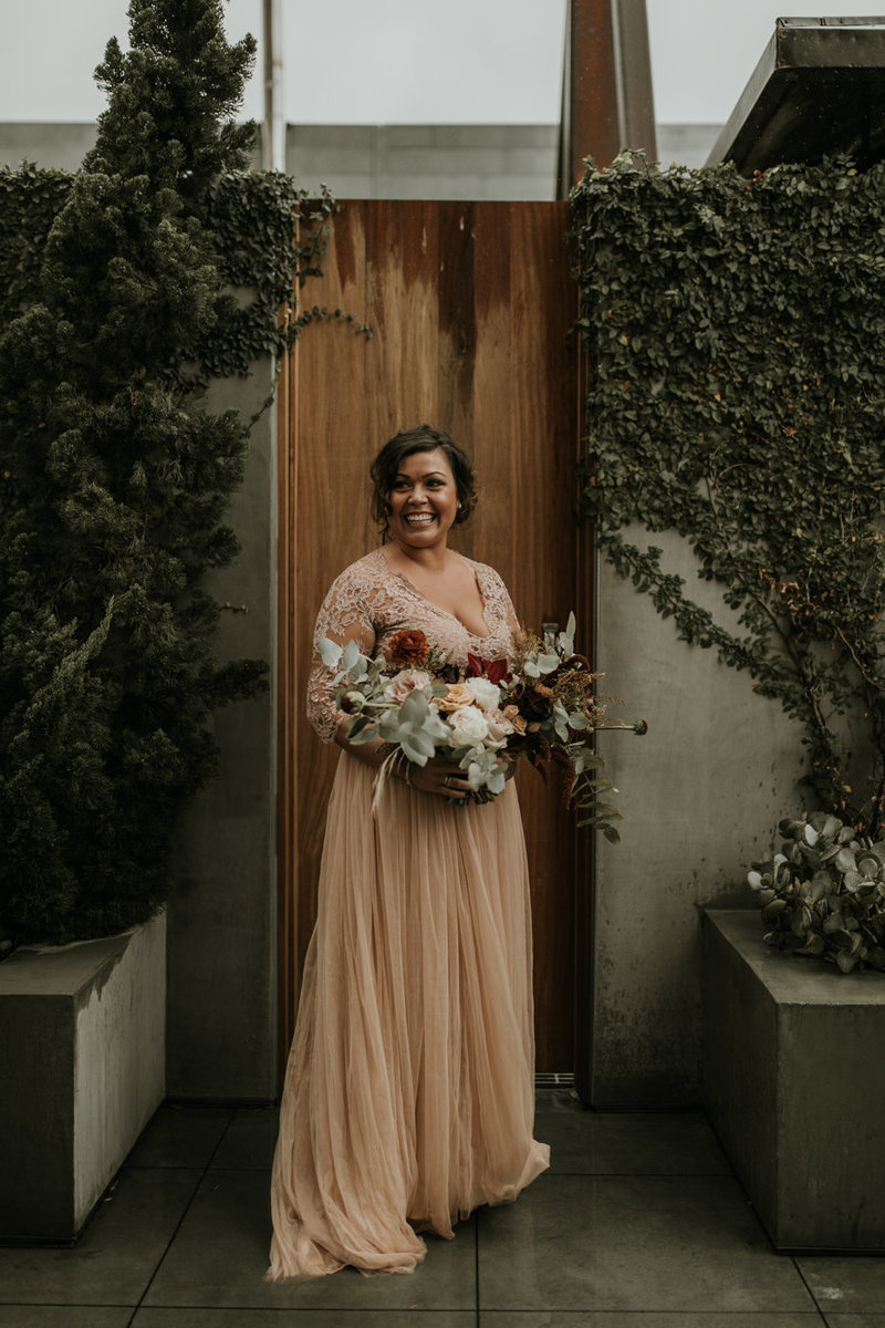 Bride in blush wedding dress and dramatic bridal bouquet at this Natural History museum wedding on New Years Eve