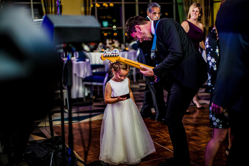 Band member plays with flowergirl at Sheraton Erie Bayfront Hotel wedding reception