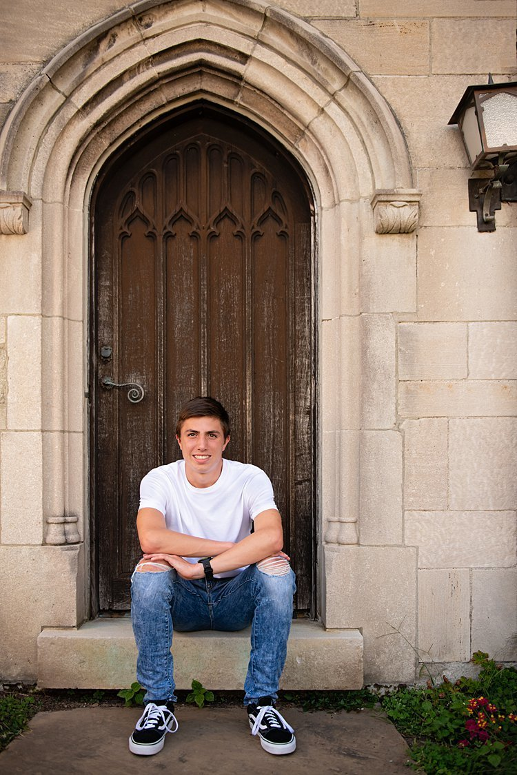 High school senior boy seated in front of brown door at Hartwood Acres in Pittsburgh, PA
